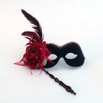 Black folding stick mask with red feather and red rose